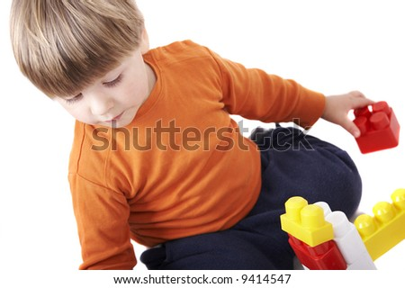 A small toddler boy playing with construction toy. Isolation on white, focus on face. - stock photo