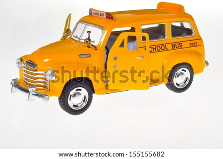 A small toy school bus over white - stock photo