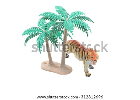 A small toy tiger with trees isolated on a white background. - stock photo