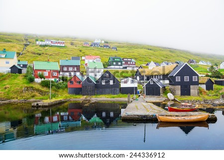 A small village on one of the Faroe Islands. The gloomy weather. Fog. - stock photo