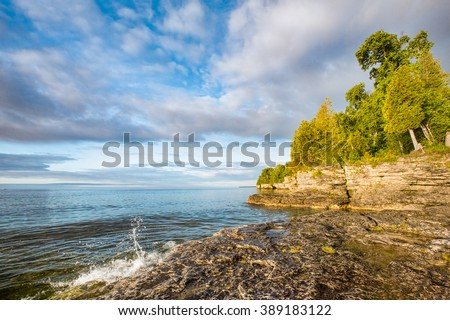A small wave breaks and splashes under a cloudy blue sky at Door County, Wisconsin's Cave Point on the coast of Lake Michigan. - stock photo