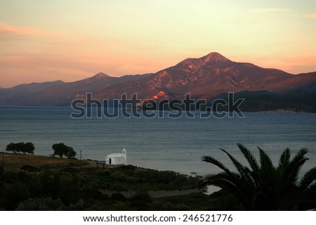 A small white church on the Aegean coast at sunset on the Greek island of Samos, in the background of the Turkish mountains - stock photo