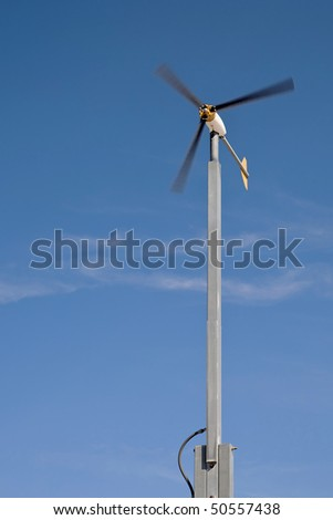 A small wind turbine spins to provide clean energy. - stock photo