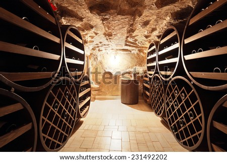 A small wine cellar with silence on the shelves of wine bottles, nobody - stock photo