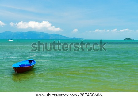 A small wooden boat moored on a beach in Thailand - stock photo