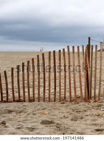 A small wooden fence in the sand by the beach.