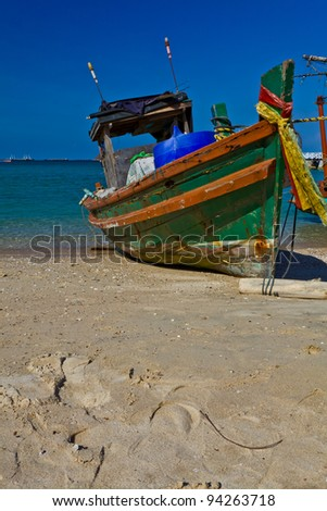A small wooden fishing boat is run aground on the beach, Si-Chang island, Thailand