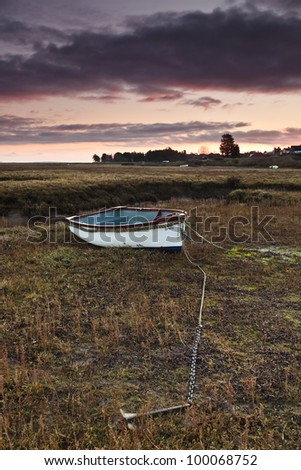 A small wooden fishing boat on the coastal marshes of the North Norfolk coast - stock photo
