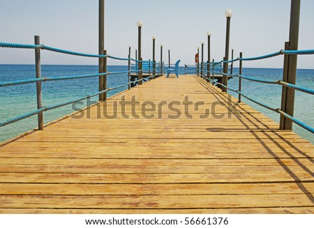 A small wooden jetty going into the sea from a tropical beach
