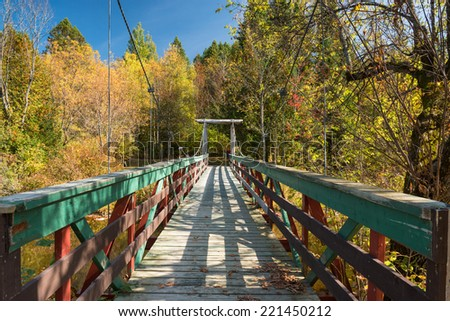 A small wooden suspension bridge in the quebec countryside - stock photo