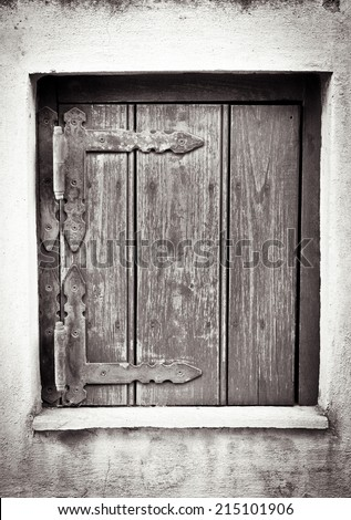 A small wooden window shutter in a white wall in sepia - stock photo
