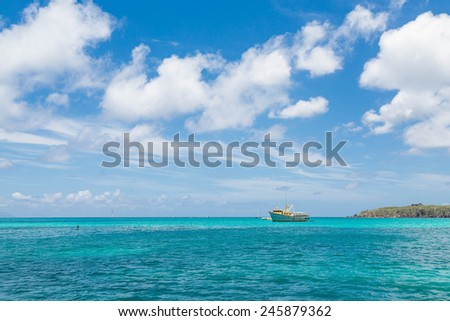 A small yellow and white fishing boat moored on the horizon of a blue Caribbean harbor