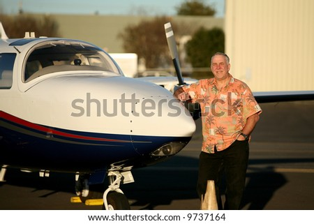 a smart and well to do man stands proudly next to his latest airplane for his photo - stock photo