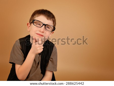 A smart little boy is wearing glasses thinking about something with his hand on an isolated tan background for an education or concentration concept. - stock photo