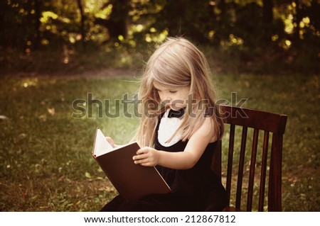 A smart little girl is reading an old book in nature with trees in the background for an education or knowledge concept. - stock photo
