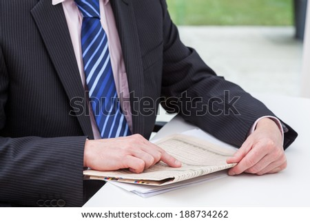 A smartly dressed businessman reading his daily newspaper