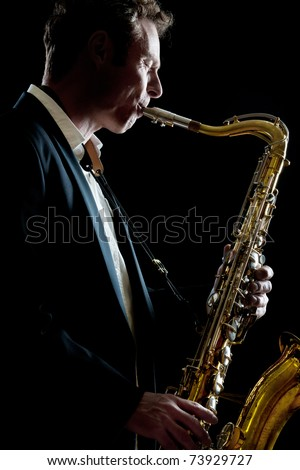A smartly dressed saxophone player in a dark club setting - stock photo