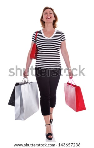 A smartly dressed woman in her early 40s carrying shopping bags, isolated on a white background. - stock photo