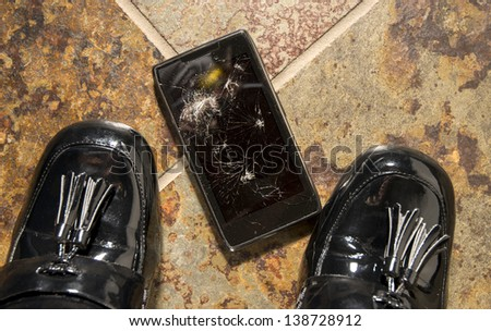 A smartphone lies broken between the shoes of its businesswoman owner just after being dropped.