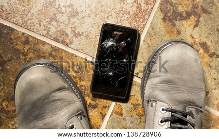 A smartphone lies broken between the workboots of its owner just after being dropped.