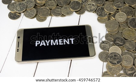 A smartphone with coins and wooden background. Financial concept.