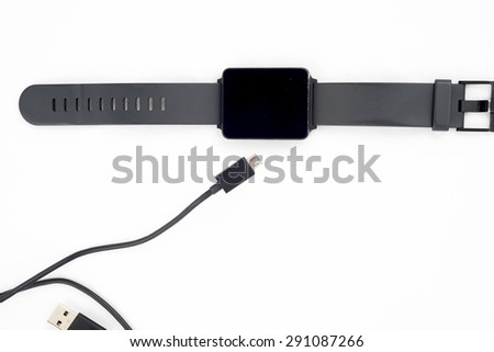 A smartwatch drapped in a usb charging cable. - stock photo