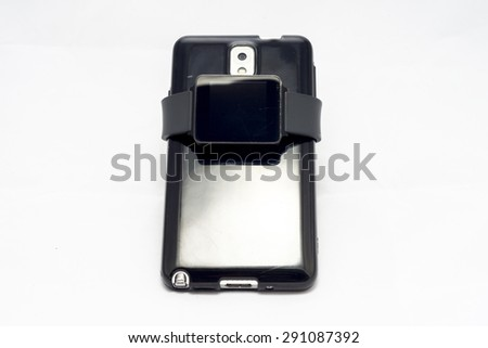 A smartwatch symbolicaly wrapped around a smartphone to emphasise the need of a smartphone for a smart watch to function. - stock photo