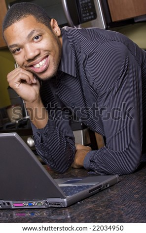 A smiling african american man on his laptop in the kitchen