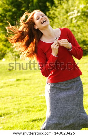 A smiling and jumping young Caucasian female holding some daisies in her hands. - stock photo