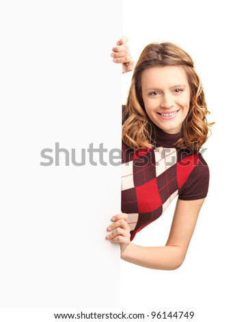 A smiling beautiful girl posing behind a white panel isolated on white background - stock photo