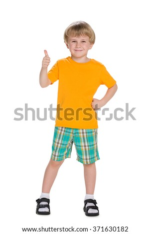 A smiling blond little boy holds his thumb up - stock photo