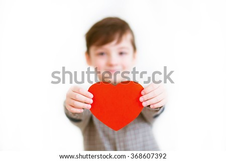 A smiling boy in a plaid shirt with a red heart in his hands. - stock photo