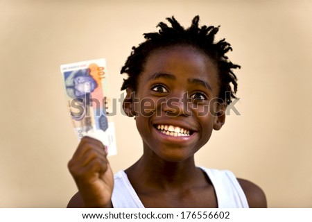 A smiling boy with a white sleeveless shirt holding money. - stock photo
