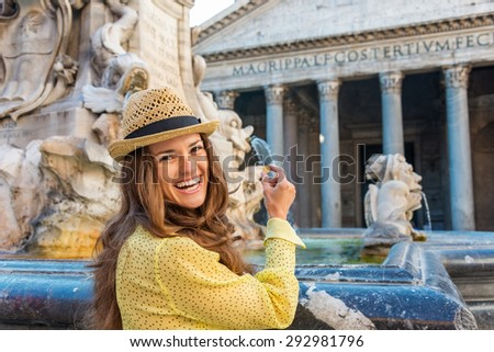 A smiling brunette tourist holds a coin up as she prepares to throw it into the Pantheon fountain. Behind her, the Pantheon fountain and Pantheon in summer. - stock photo