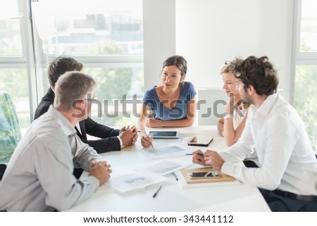 A smiling business executive is leading a project at an office business meeting. She is sitting at the end table with her team around her in a luminous white open space, brainstorming some new ideas.