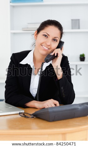 A Smiling businesswoman on the telephone in her office
