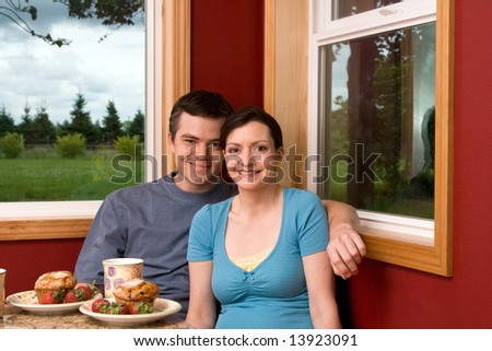 A smiling couple having breakfast by a large window at home.  The man has his arm around the woman.  Both are looking at the camera.  Horizontally framed shot. - stock photo