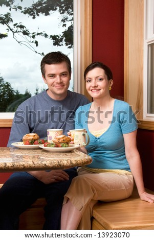A smiling couple sitting and eating breakfast by a large window at home.  Vertically framed shot. - stock photo