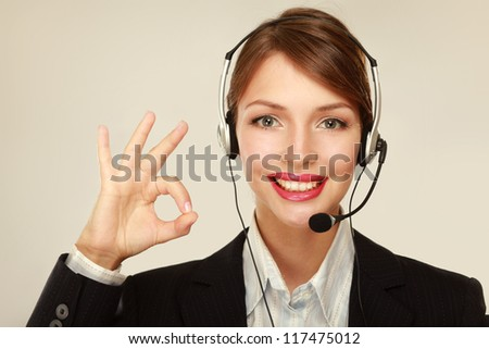 A smiling customer service girl showing ok, isolated on white background - stock photo
