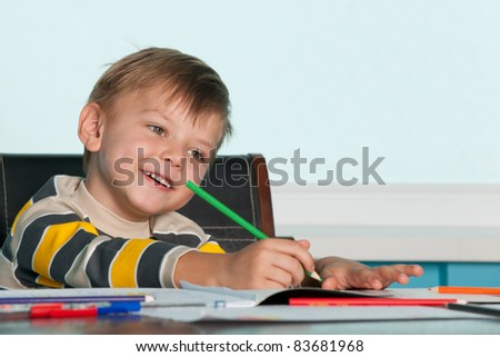 A smiling drawing little boy is sitting at the table - stock photo