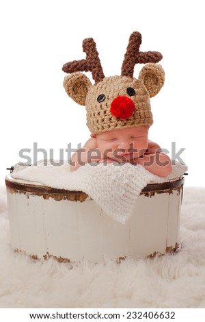 A smiling eight day old newborn baby boy wearing a red nosed reindeer hat and sitting in an antique wooden bucket. Photographed in a studio on a white background. - stock photo