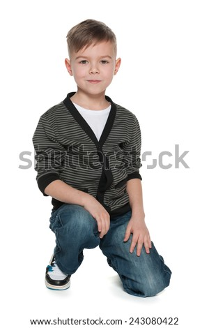A smiling fashion little boy sits on the white background