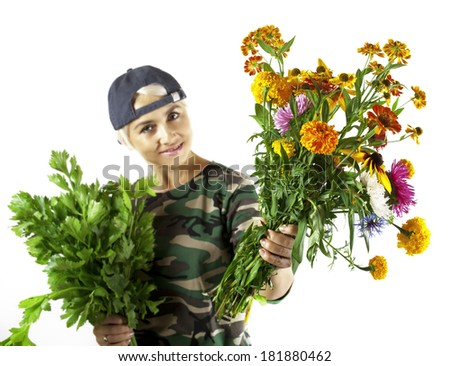 A smiling girl in camouflage offers a bouquet of garden flowers - stock photo