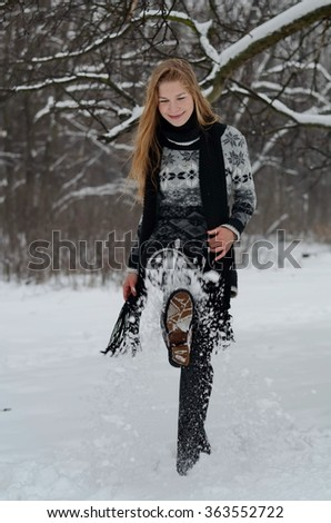 A smiling girl in in a grey sweater and a long black scarf plays with snow outdoors, winter day in the park.