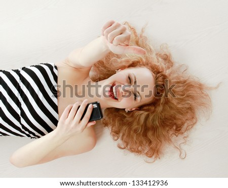A smiling girl lying on the floor with a mobile phone and showing ok - stock photo