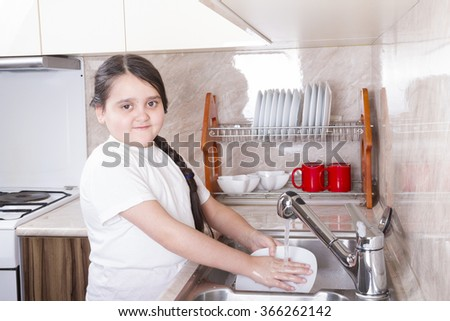 A smiling girl plate rinse under water