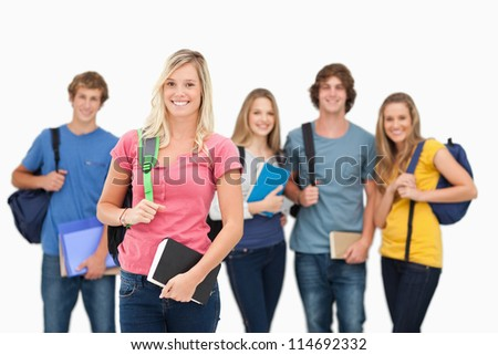 A smiling girl stands in front of her friends as she looks into the camera - stock photo
