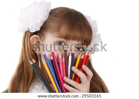 A smiling girl with color pencils in hands on a white background Schoolgirl is holding coloured pencils. - stock photo