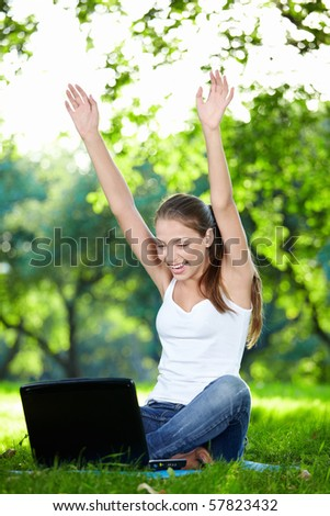 A smiling girl with his hands up a laptop in the park - stock photo