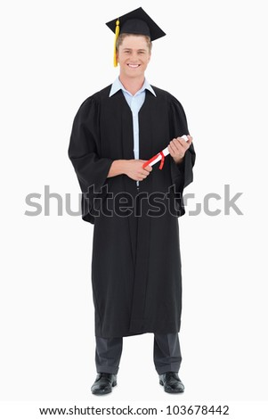 A smiling graduate with his degree in hand as he looks at the camera - stock photo